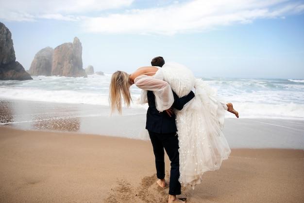 男性は女性を肩に抱え、彼らは海のビーチにいます 無料写真