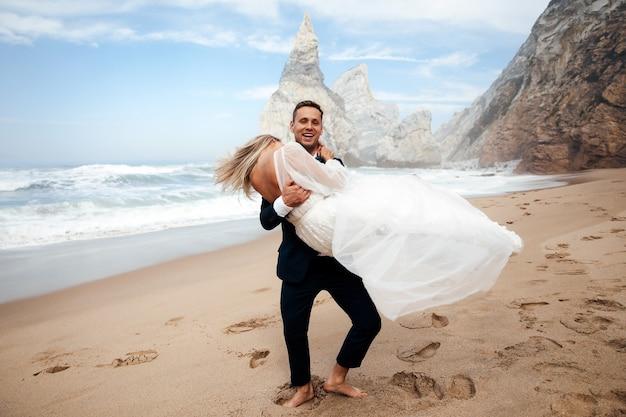 男は妻を手に持っており、彼らはとても幸せそうに見える 無料写真