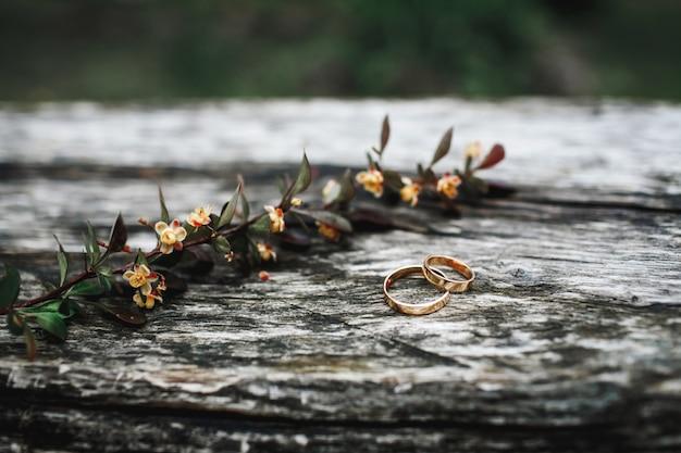 結婚指輪のペアは、花の枝の近くの木製の表面にあります。 無料写真