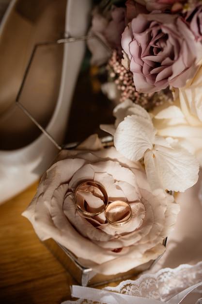 Обручальные кольца лежат на розе Бесплатные Фотографии