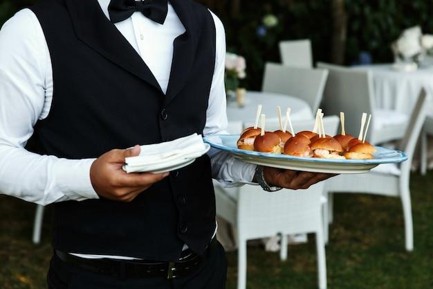 ウェイターはおいしい軽食とプレートを運ぶ 無料写真