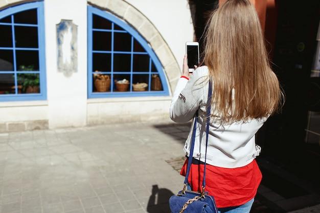 女の子は彼女の電話で青い窓の写真を撮る 無料写真