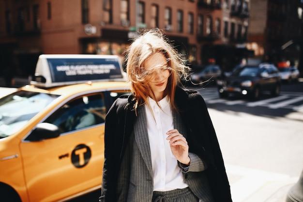黒いコートのブロンドの女性は、ニューヨーク市のどこかの日当たりの良い通りに立っています 無料写真