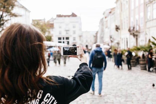 女性、スマートフォンで市街広場の写真を撮る 無料写真