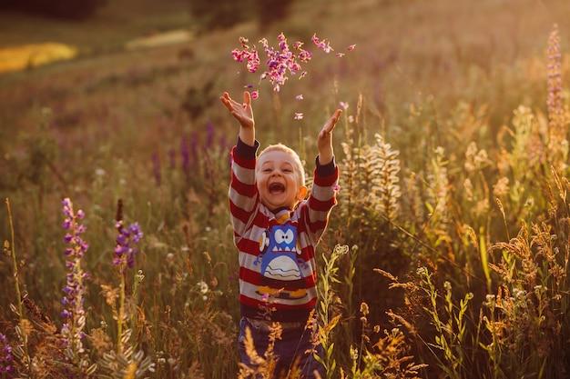 朗らかな子供が花びらを投げると、ラベンダーの野原でポーズをとります 無料写真