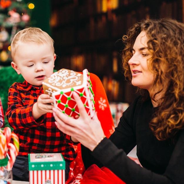Мама веселится со своим сыном, сидящим в комнате, одетым на рождество и новый год Бесплатные Фотографии