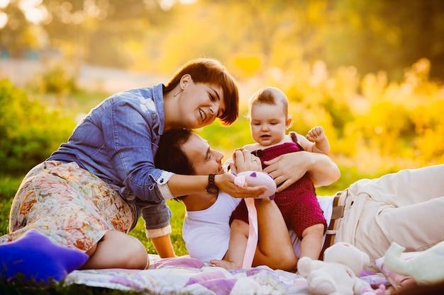 Родители играют с маленькой девочкой на одеяле в лучах вечернего солнца Бесплатные Фотографии