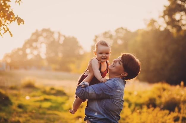 Женщина веселится с маленькой девочкой, стоящей в лучах золотого солнца Бесплатные Фотографии
