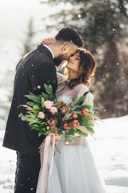 Бородатый мужчина и его прекрасная невеста позируют на снегу в волшебном зимнем лесу Бесплатные Фотографии