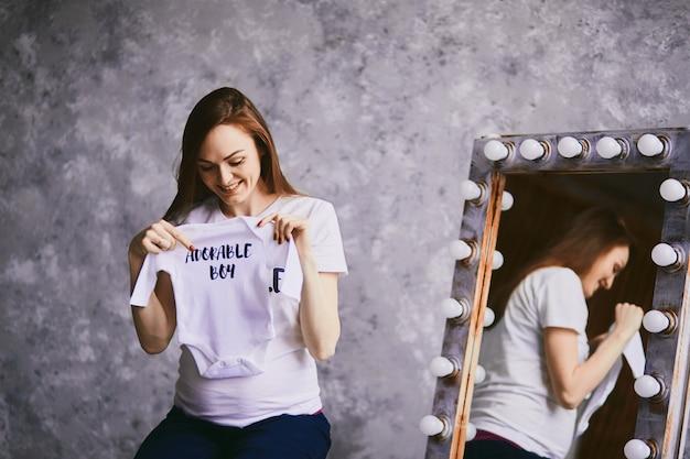 Будущая мать держит рубашку для ребенка Бесплатные Фотографии