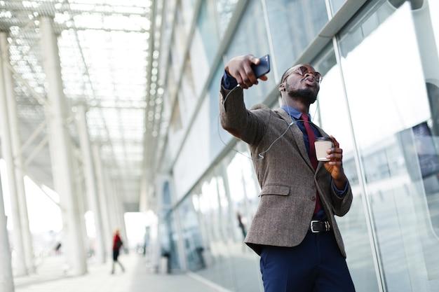 Счастливый афро-американский деловой человек танцует, слушая музыку Бесплатные Фотографии
