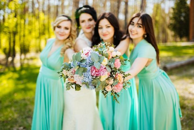 結婚式の花束と花嫁と花嫁介添人。晴れた結婚式の受信は楽しい瞬間。 無料写真