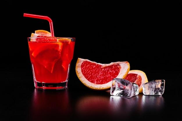 Кровавый оранжевый джин и тонизирующий коктейль с ломтиками апельсина и льда в стакане Бесплатные Фотографии