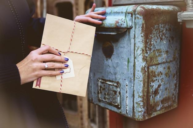 女性は、古いヴィンテージのメールボックスでサンタクロースの封筒をスローする 無料写真