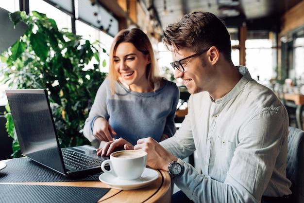 カラフルで笑うカフェに座って、ラップトップの画面を見ているカップル 無料写真