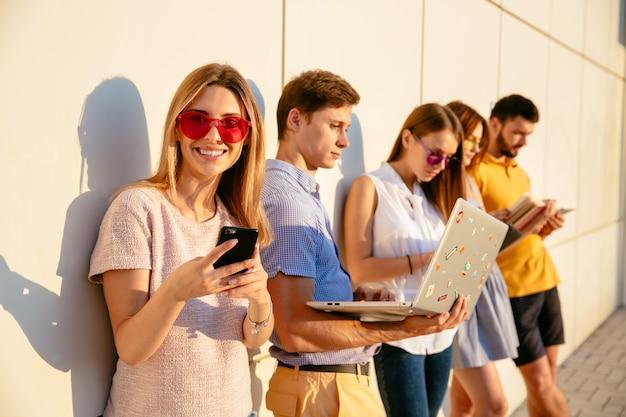 Красивая женщина в розовых солнцезащитных очки, улыбка на камеру и с помощью мобильного телефона. Бесплатные Фотографии