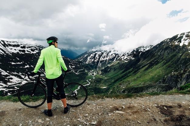 Велосипедист, стоящий с дороги велосипеды на фоне красивых альпийских гор пейзаж Бесплатные Фотографии