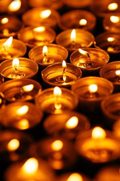 燃えるろうそく。多くの黄色のろうそくが暗く輝きます。閉じる 無料写真