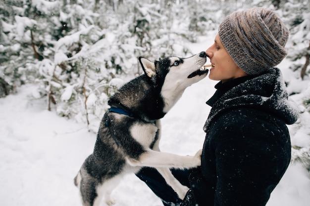 冬の雪の天気で屋外で口から口に彼のハスキー犬のビスケットを人が給餌する 無料写真