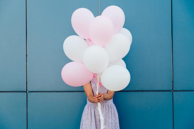 青い壁に立って、風船の束と彼女の顔を隠す若い女性。 無料写真