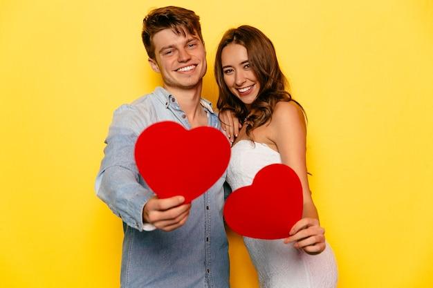 赤い心を保持して、完璧な美しいカップル聖バレンタインデーを祝う 無料写真