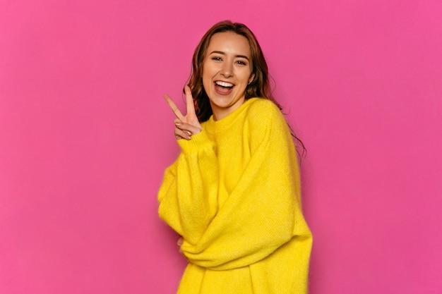 豪華な若い女性は、黄色のセーターを着て平和のジェスチャーを示しています。 無料写真