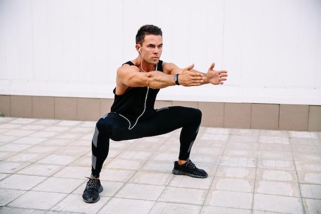 若い、集中した、スポーツマン、スクワット、トレーニング、屋外で 無料写真