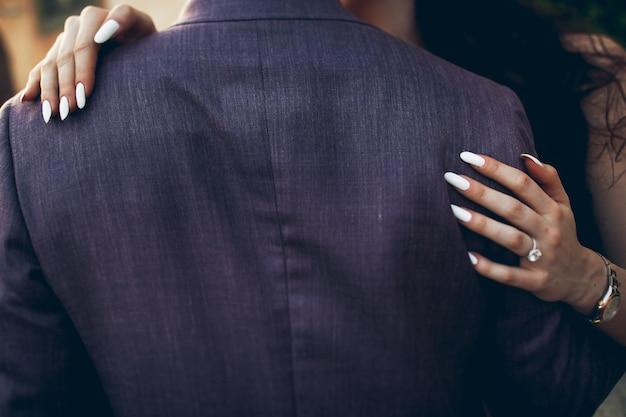 白い爪の女性の手は男の背中にある 無料写真