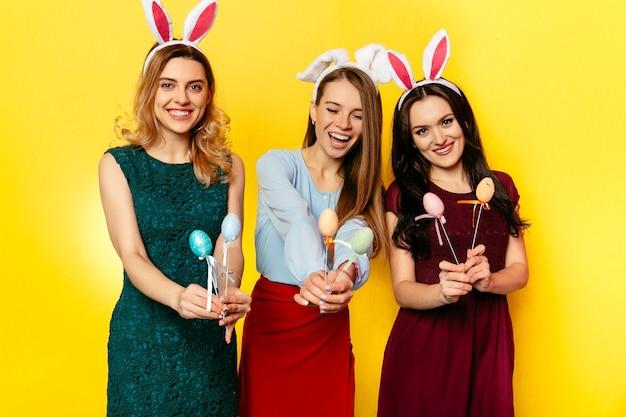 イースター。イースター、おめでとう。ウサギの耳のおかしい女性たちが一緒に楽しい、休日を祝う 無料写真