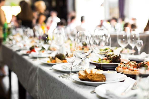 結婚式のために準備された長いテーブルの上に輝くガラス製品 無料写真