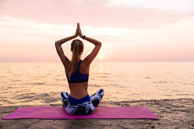 Йога на рассвете. спортивная женщина, практикующий йогу, сидя на пирсе в позе лотоса Бесплатные Фотографии
