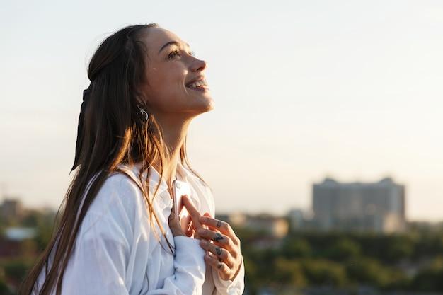 Красивая молодая женщина улыбается нежно стоять на крыше в лучах вечернего солнца Бесплатные Фотографии