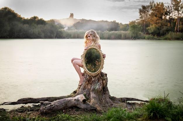ブロンドの裸の女性は、霧で覆われた湖の前に座っている鏡を保持しています 無料写真