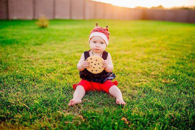 大規模なチョコレートクッキーを持つ小さな女の子は、裏庭に座っている 無料写真