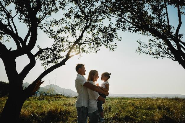 古い木の下で娘と遊ぶ素敵な両親のシルエット 無料写真