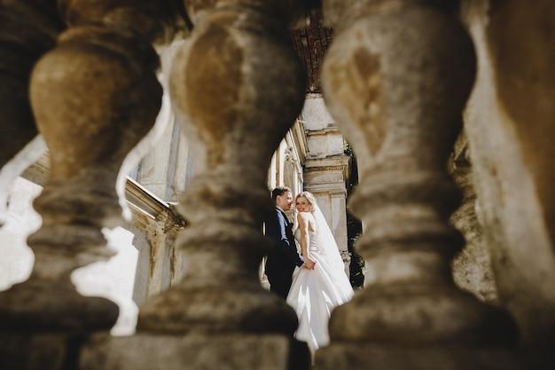 古代の建物の近くに立っている魅力的な花嫁 無料写真