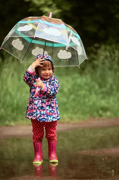 傘を持つ魅力的な少女は、雨の後にプールのガンブートに立って楽しい 無料写真