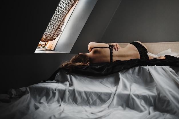 Женщина в черном белье лежит на серой кровати перед окном Бесплатные Фотографии