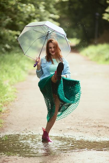 緑のスカートの美しい若い女性は、雨の後にプールのガンプットで歩いて楽しい 無料写真