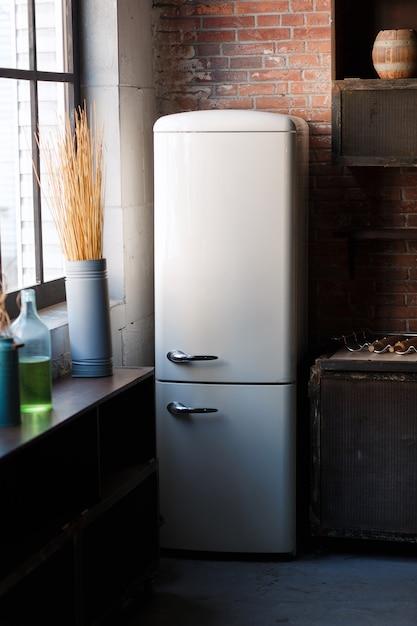 白いモダンなレトロな冷蔵庫、素朴なレンガの壁のある暗い質感のある色のキッチンインテリア 無料写真