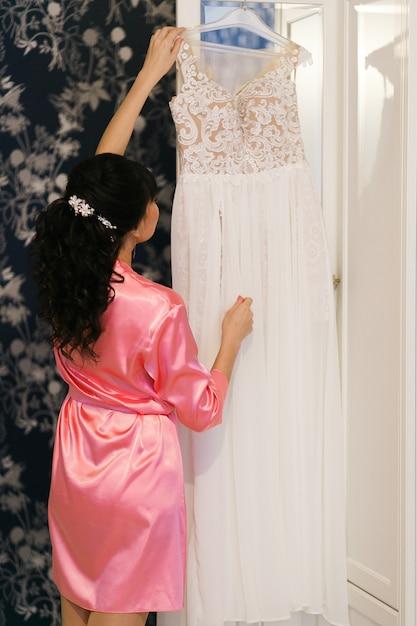 花嫁の朝の準備。ウェディングドレスを持つピンクのバスローブの女性 無料写真