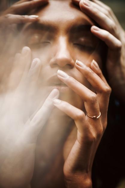男は彼女の優しい指を唇につけている間に女性の頭を柔らかく保つ 無料写真