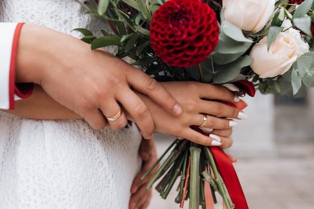花嫁と新郎は、彼らの腕の中で豊富な赤い結婚式の花束を保持 無料写真