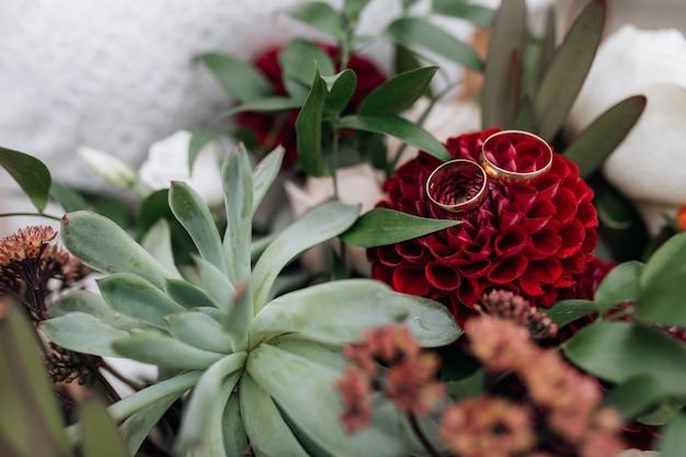 優雅な黄金の結婚指輪は、花嫁の花束の赤い花に横たわっています 無料写真