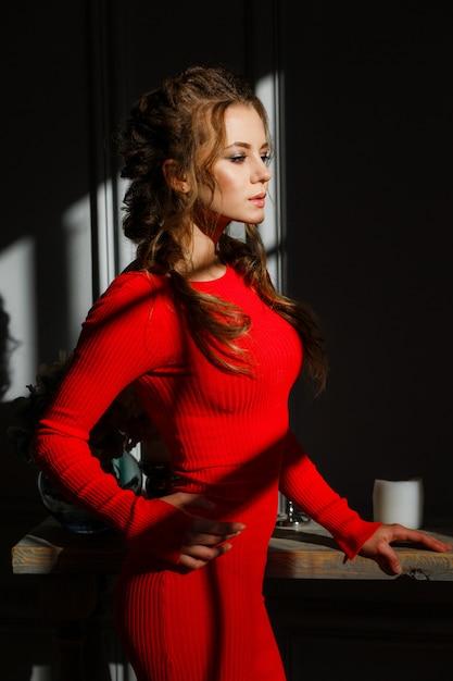 美しいセクシーな若い女性は、灰色の背景に赤いドレス 無料写真