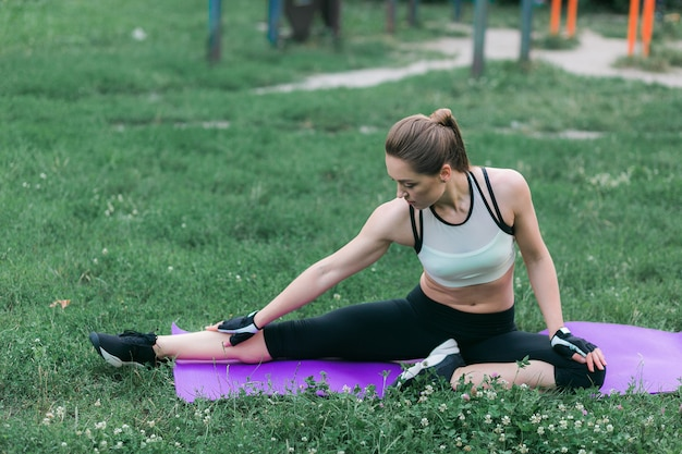 スポーツウェアにフィットする若い女性は、エクササイズ後にストレッチを行います。 無料写真