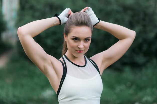 かなり若い女性が緑色の裏庭で運動する前に彼女の髪を固定する 無料写真