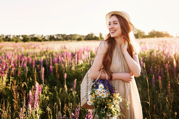 夕日の花畑で歩く幸せな若い女の子。花がいっぱいの麦わら帽子と袋を着て。 無料写真