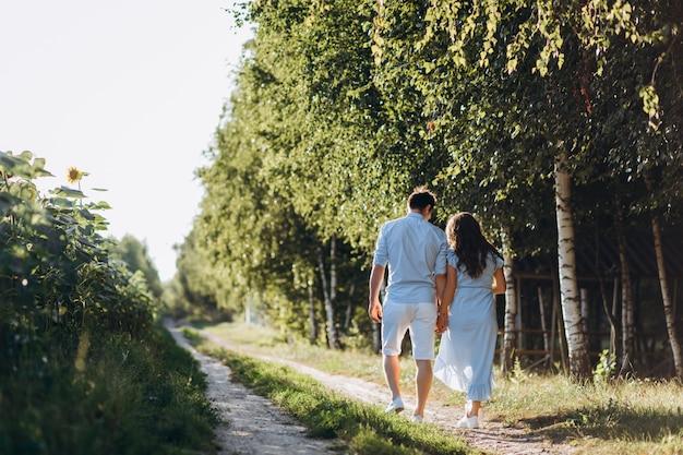 期待される男女が、ヒマワリで野原の道を歩く 無料写真