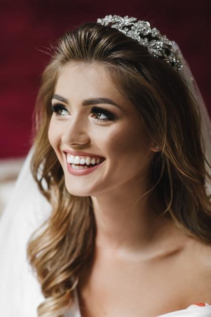 白い絹のローブの美しい花嫁はホテルの部屋のベッドに座っている 無料写真